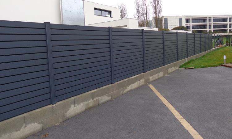 Montage d'une clôture en alu adjacente à un parking
